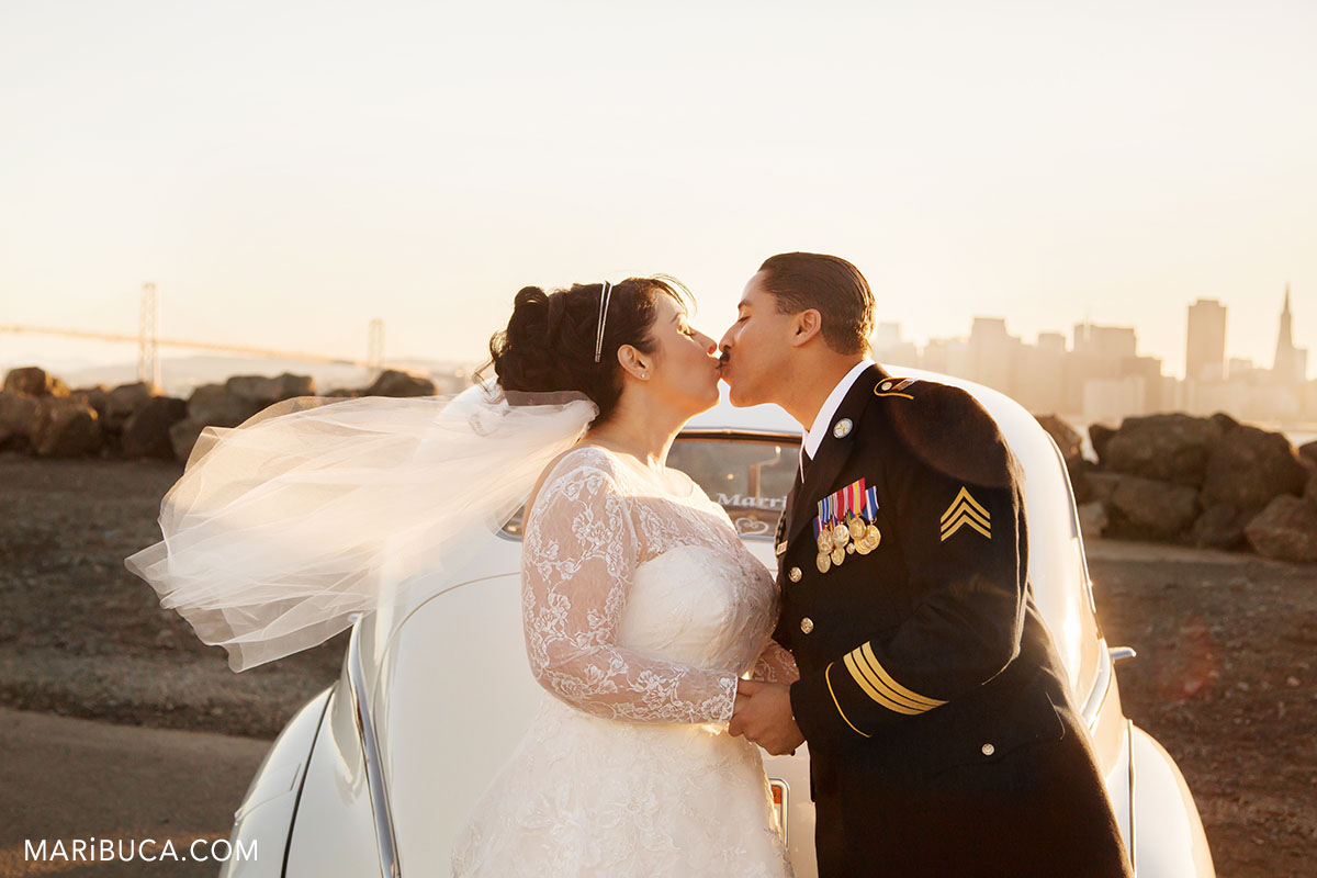 The bride and the groom are having a long kiss in the treasure island san francisco