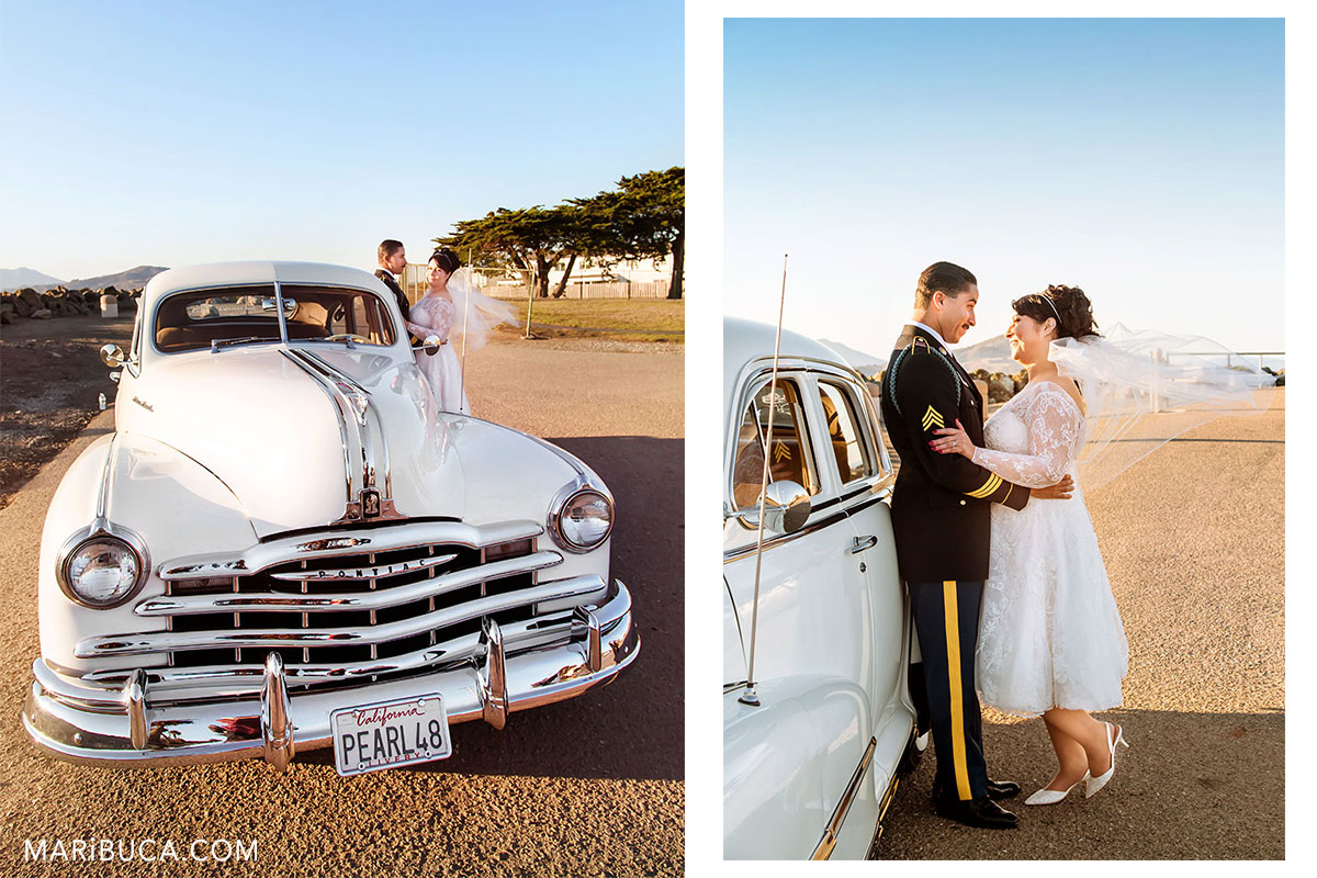 The Bride and the groom stay next to Pontiac old white car and smile each other during the perfect day in their life.