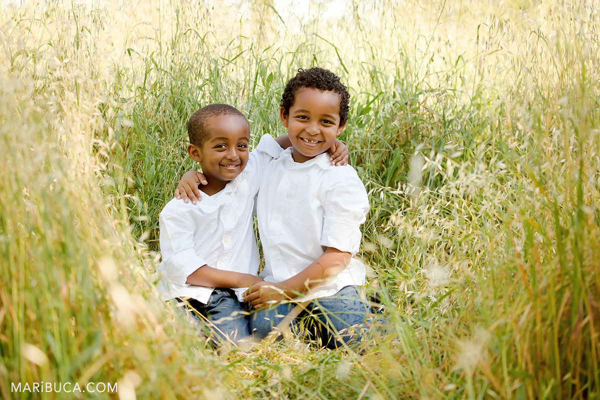 two brothers in the high grass sitting and smiling