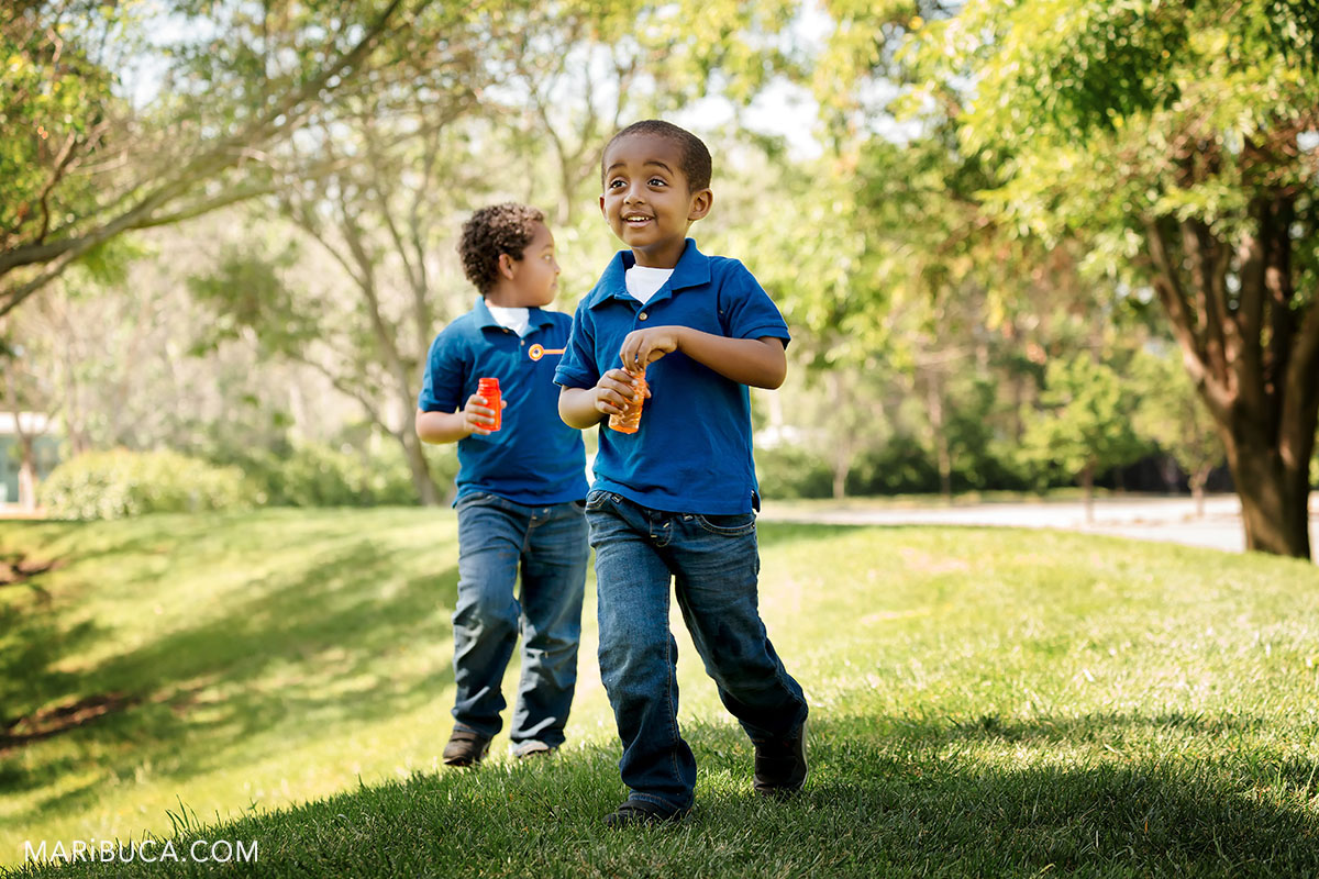 let's go to walk with soap bubbles. Two brothers boys in the blue shirts and blue jeans.