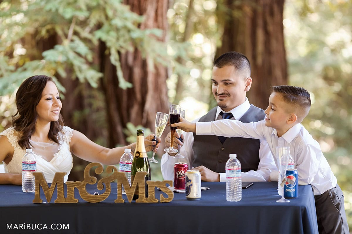 cheers in the wedding bride, groom and son in the county park.