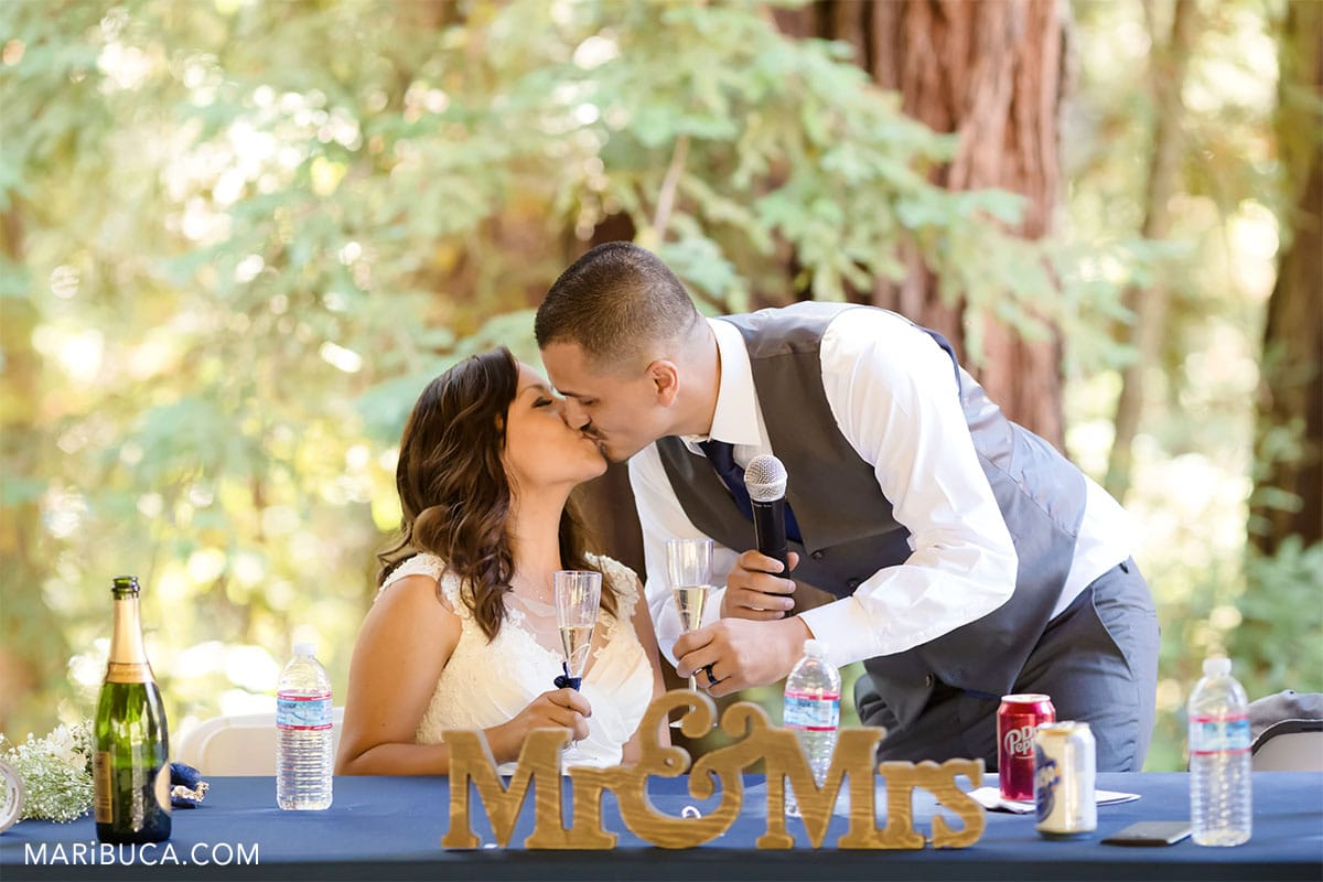 outdoor wedding bride and groom kiss each other. THe wooden signs in the table as Mr & Mrs