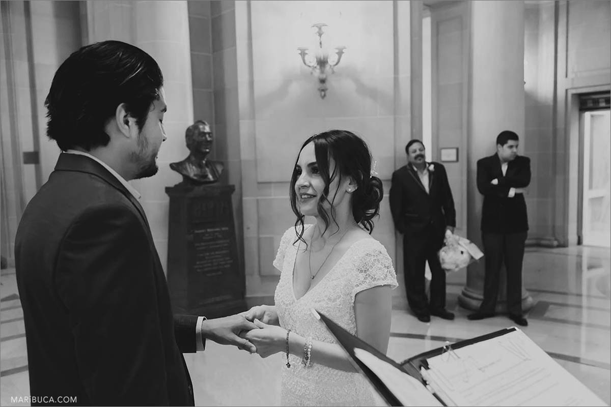 The black and white image where the bride and the groom exchange their rings and read their vows.