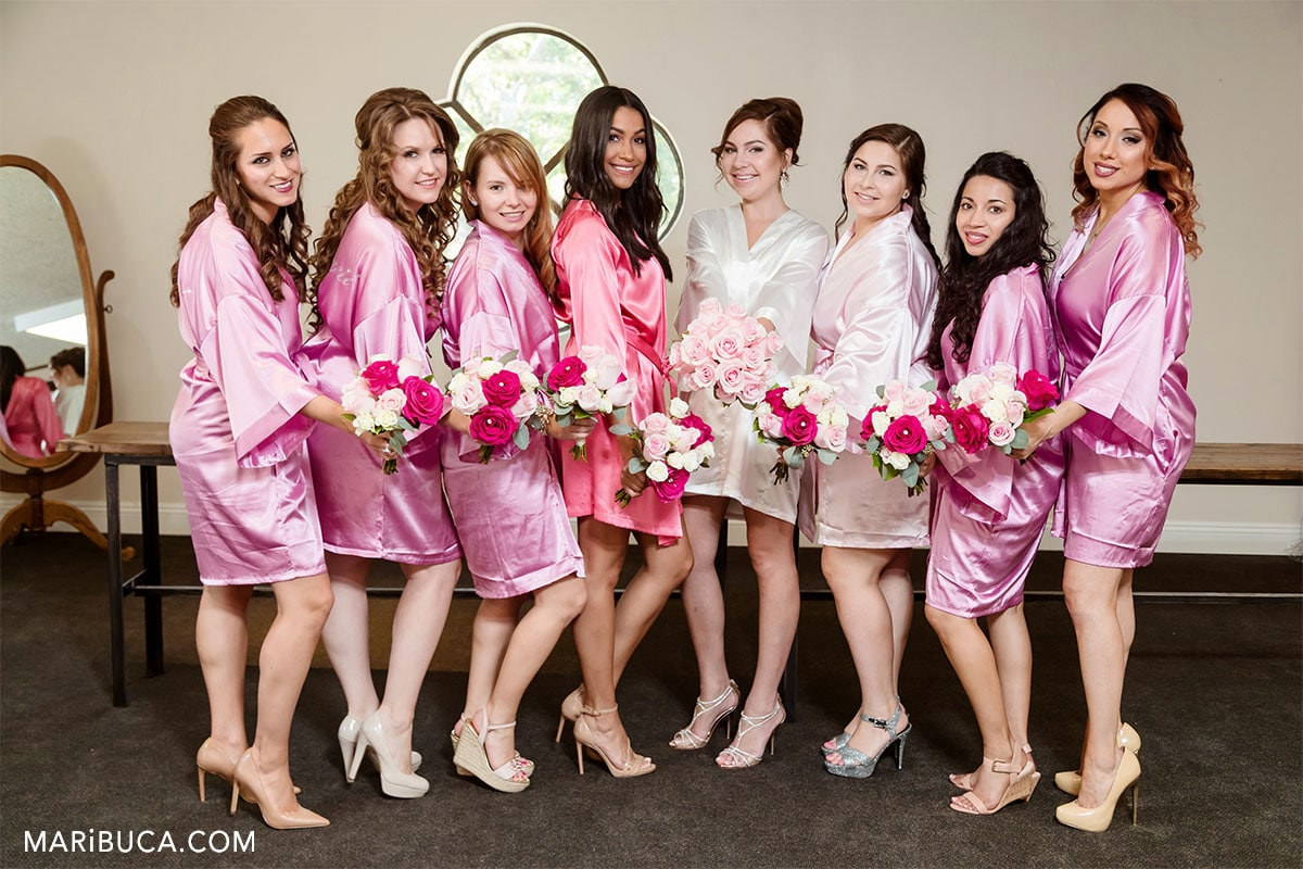 7 bridesmaids in the rose robes, and the bride before ceremony in the Wente Vineyards.