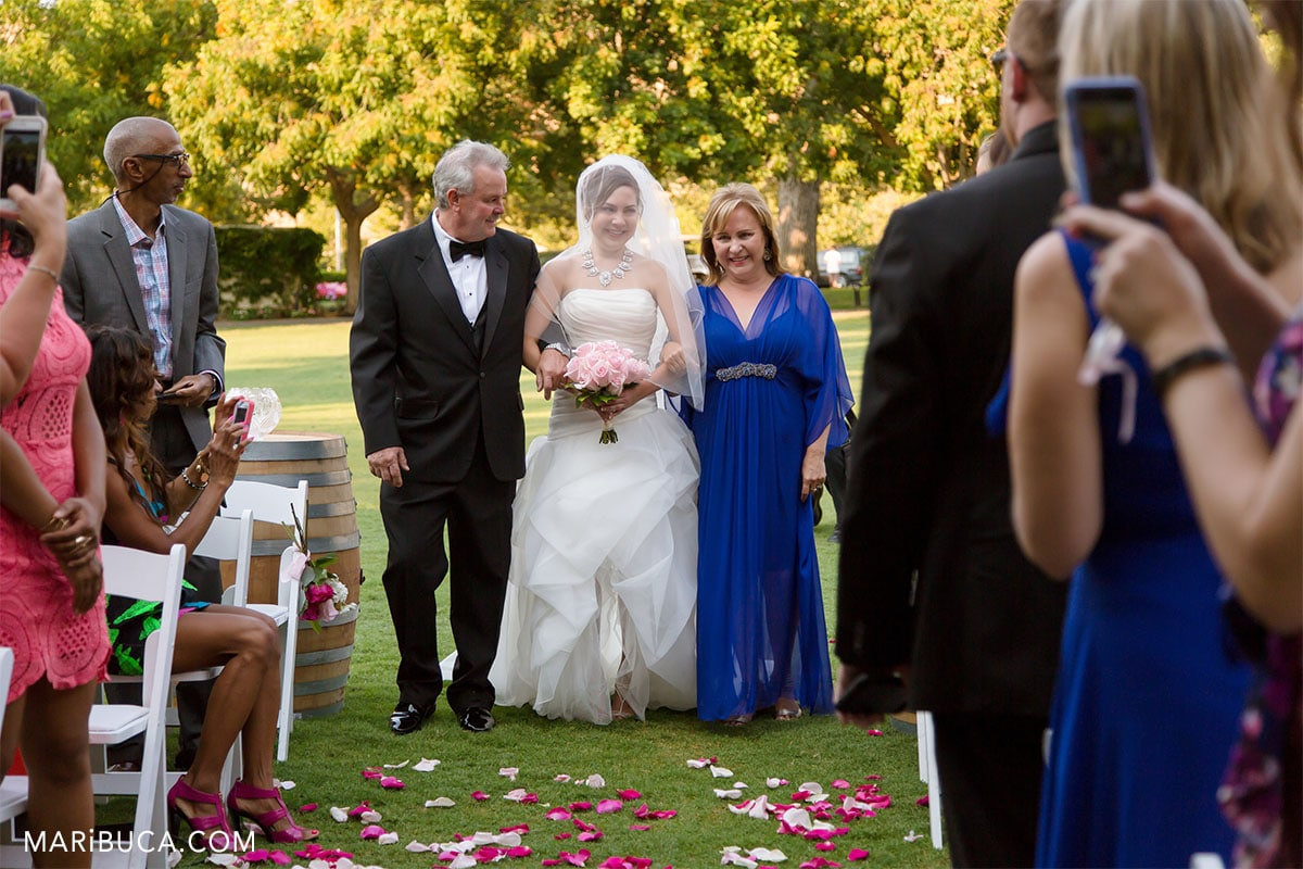 The gorgeous bride going down the aisle with her parents in the Wente Vineyards, Livermore, California