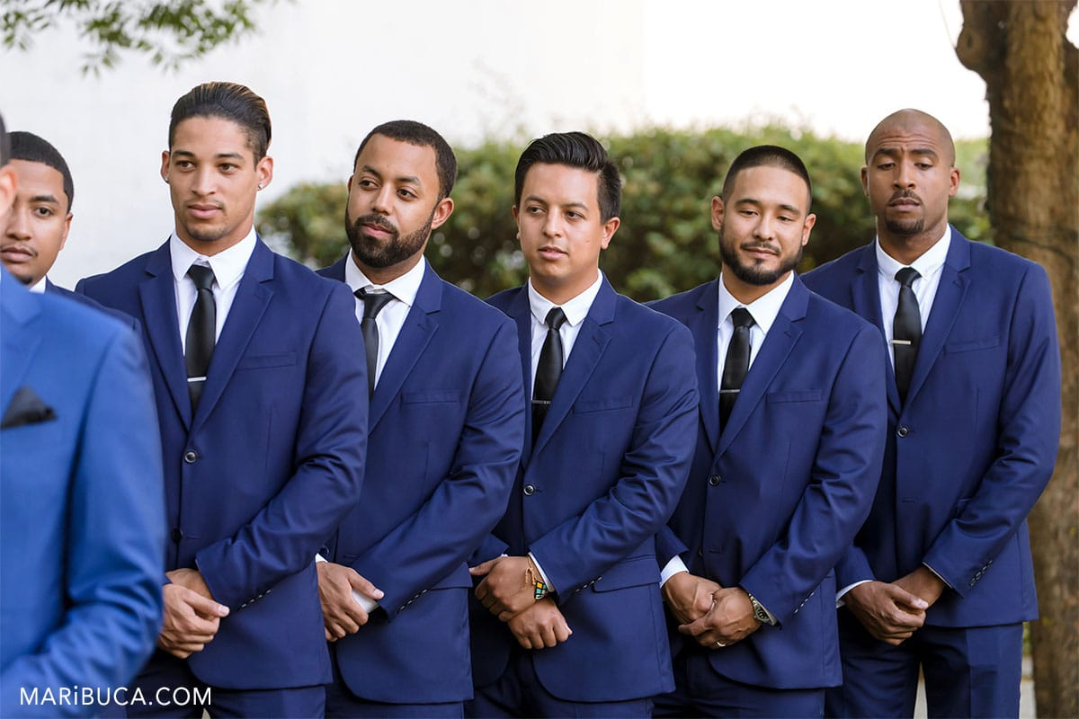 Groomsmen in the blue suits look to the groom during ceremony in the Wente Vineyards, Livermore Wedding.