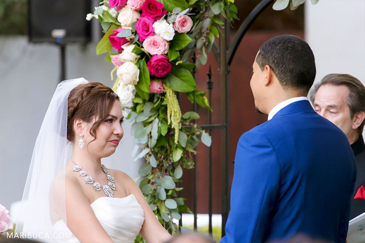 First happy bride's tears during wedding ceremony. The groom look into the bride's eyes.