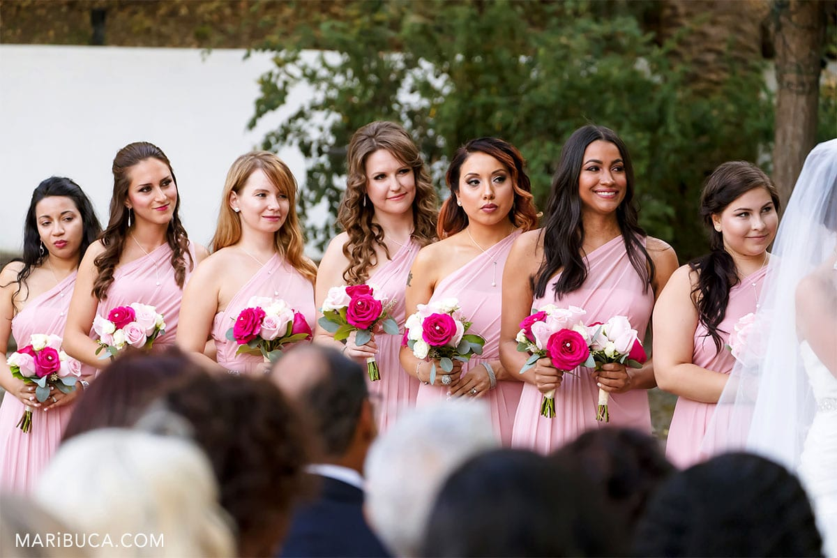 7 bridesmaids looking at the bride