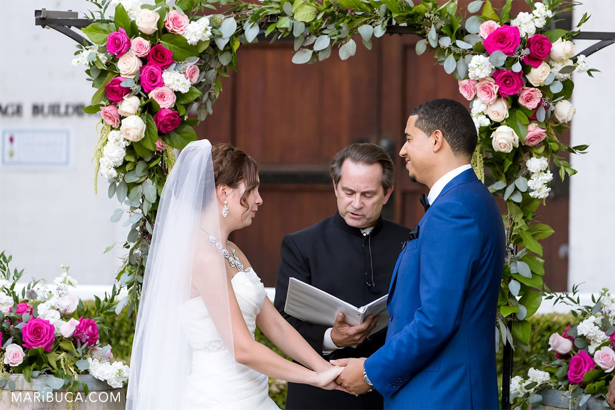 Amazing bride and handsome groom look each other in the ceremony. In this moment officiant read documents.
