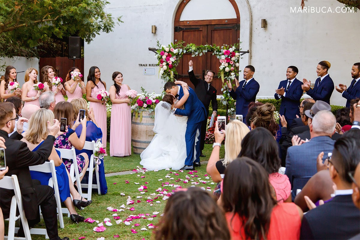 First kiss as newlyweds. Bridal party applauds, the officiant happy, guests take a video.