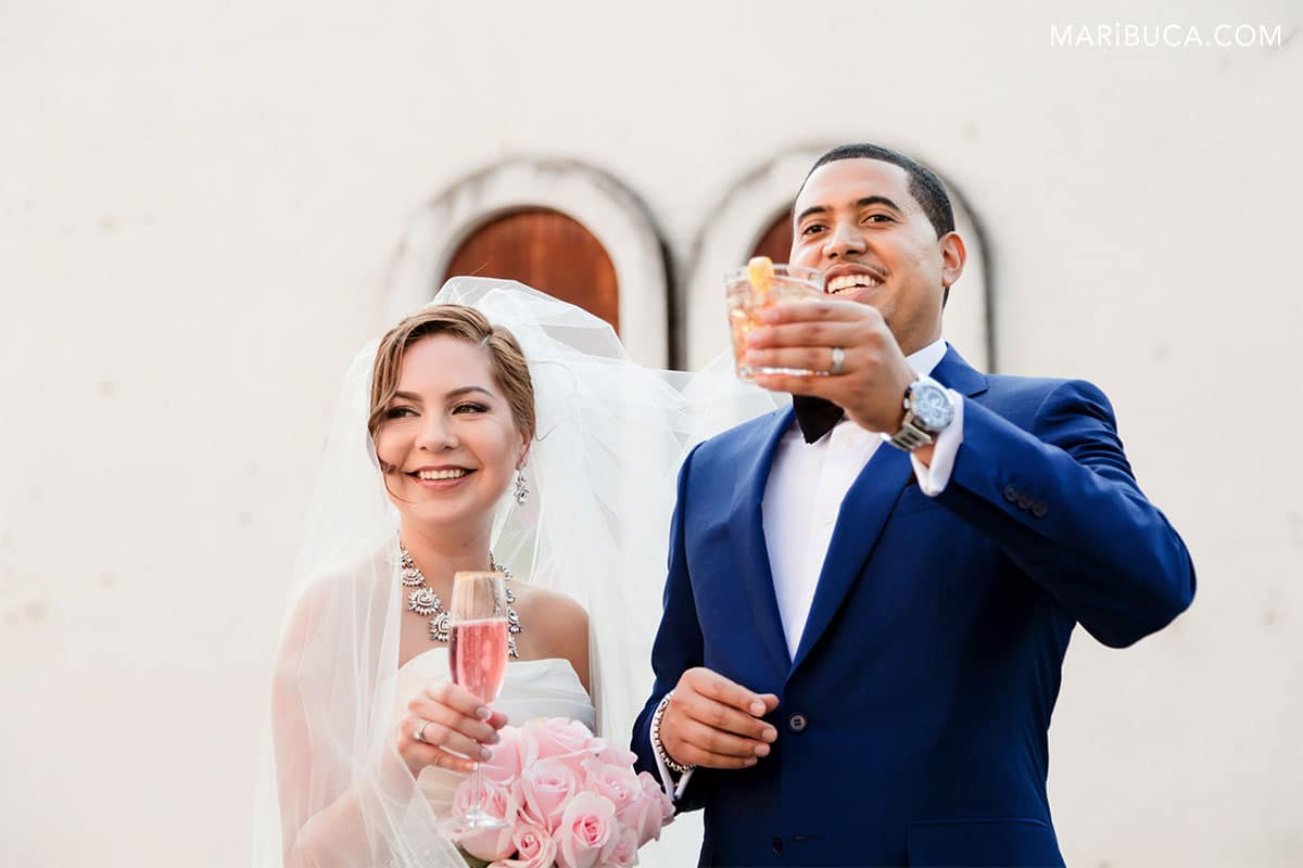 Newlyweds cheer and raised their wine glasses.