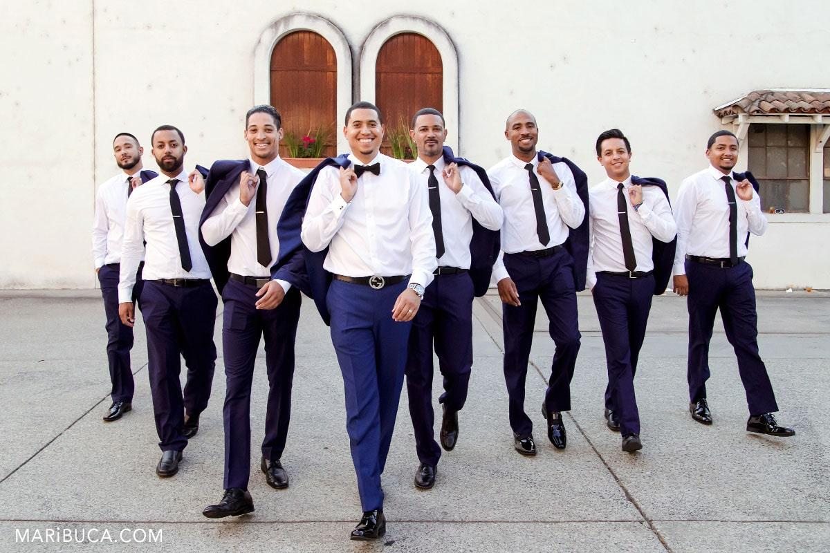 The groom and groomsmen have walking in the vineyards.