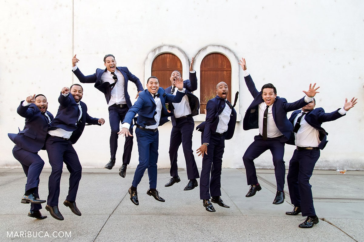 Guys with blue suits are jumping and have fun.
