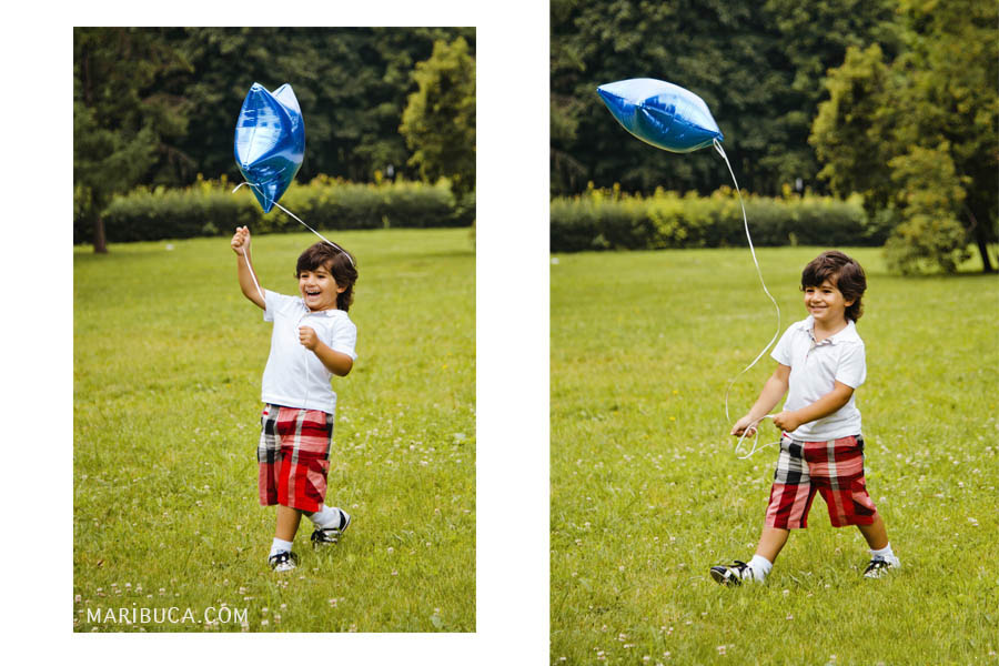 A boy in a white shirt and shorts laughs and launches a blue star-shaped balloon on green grass.