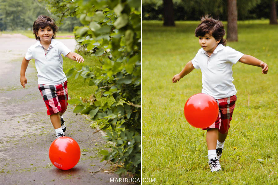Boy in white shirt and shorts in a cage plays a red ball on green grass.
