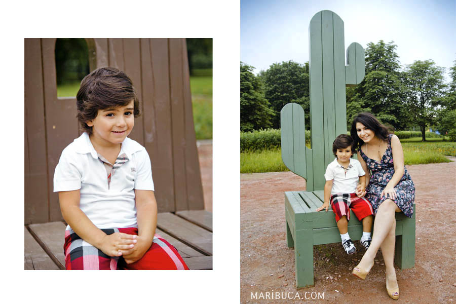 The boy sits with his mother on a green wooden chair in a seen cactus against the background of nature.
