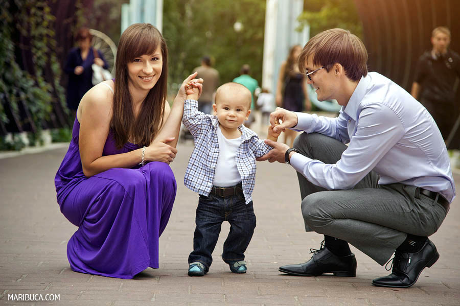 parents squatted down so that their baby son could stand comfortably and walk in the park