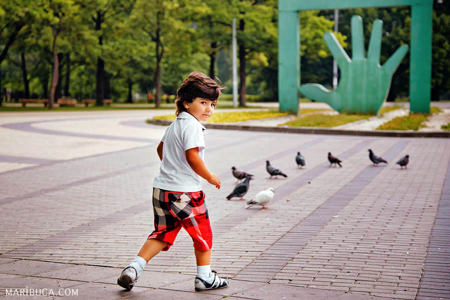 A boy in a white shirt and in red with black in a cage shorts is hunting for birds in the park.