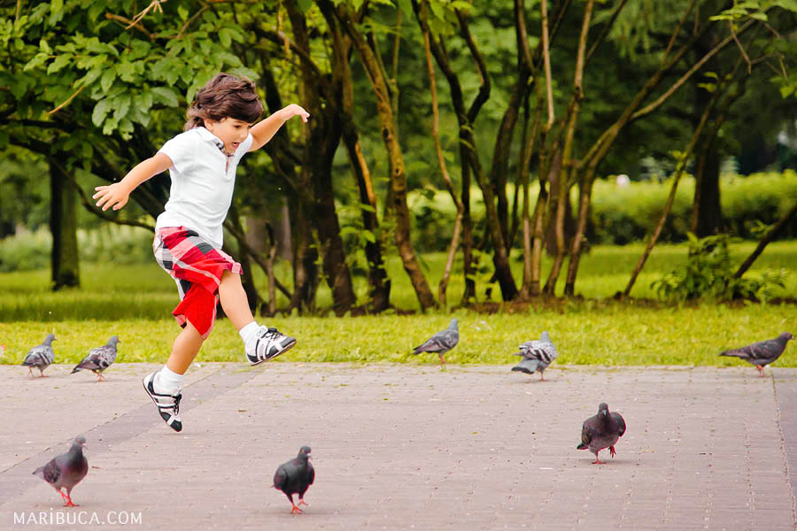 A boy in a white shirt and in red with black in a cage shorts jumping and chaising birds in the park.