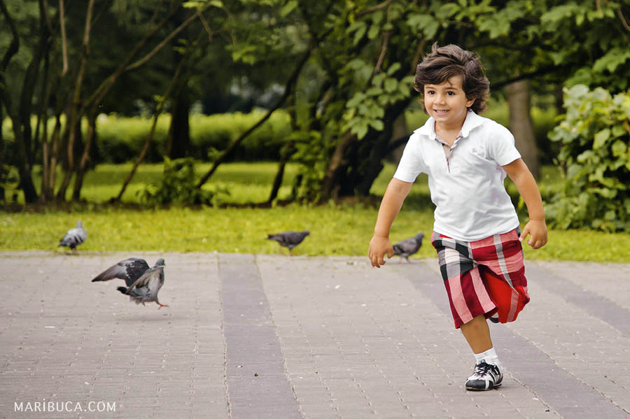 Happy 5 year old boy running in the park on a background of pigeons and green trees.