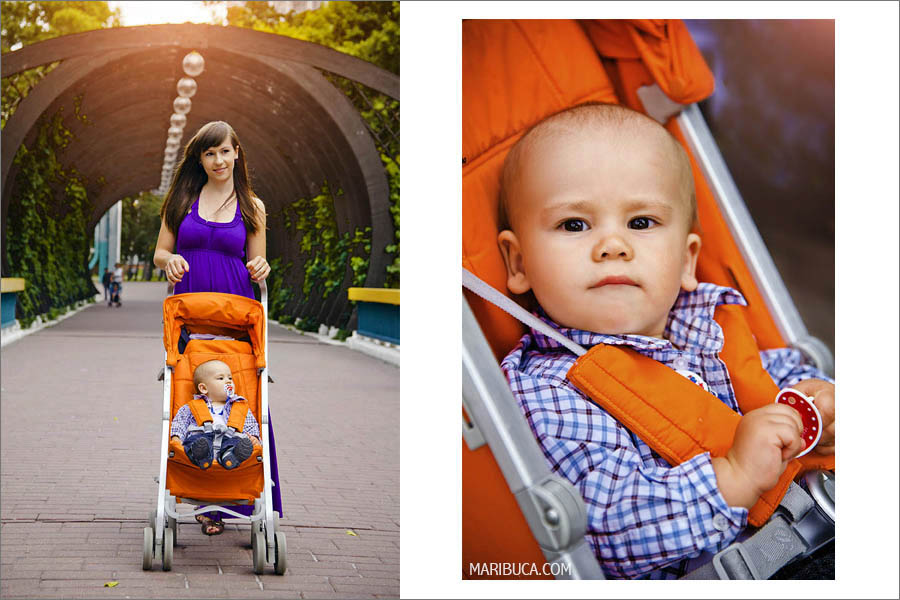 mother with a ten-month-old son walks on an orange baby carriage in the park. Portrait of the baby boy.