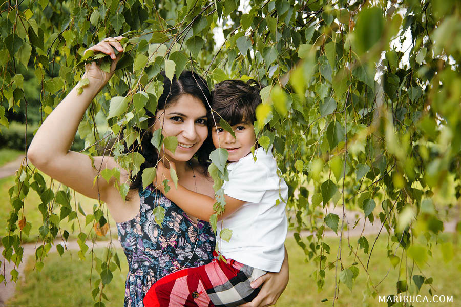 Mom and five-year-old son are hiding from the sun behind the foliage of the tree in summer weather in the Half Moon Bay.