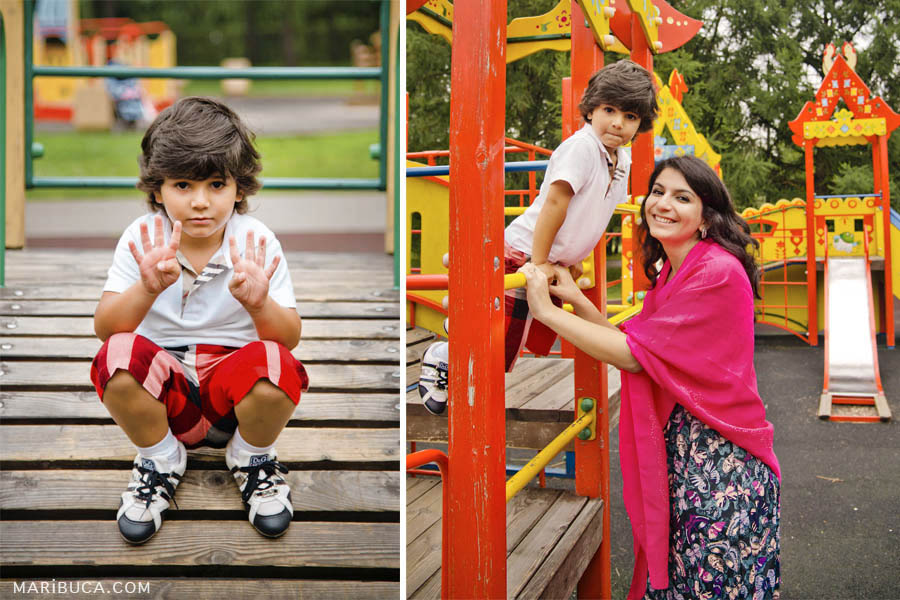 A boy in a white shirt and in red with black shorts shows how old he is. Mom with her son on the background of the playground in the children's park.