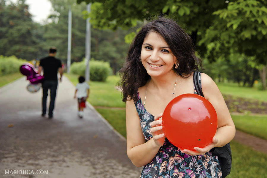 The lady is smiling and holding the red ball and her husband and son are leaving the park.