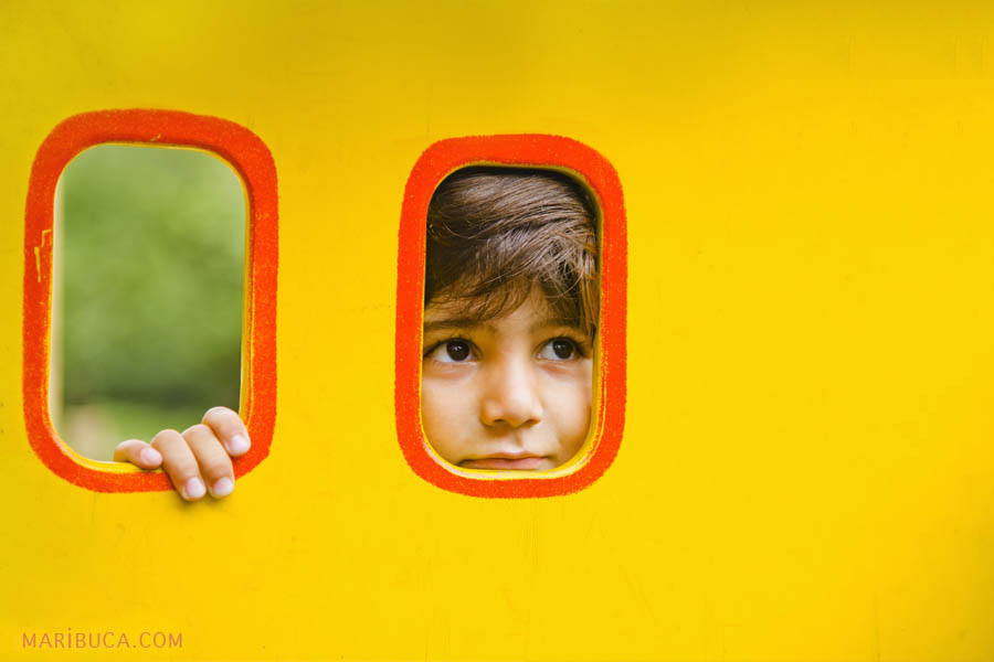 Portrait of a boy on a yellow background which looks through the window at the park.