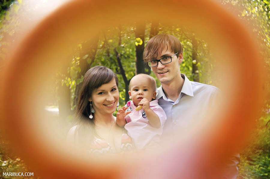 Family of the three together with orange rounded frame in the garden