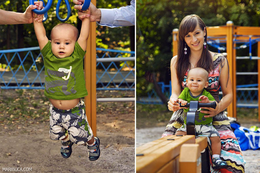 10 month old baby hangs on the Olympic rings on the playground. Mom and son baby sit on a wooden swing.