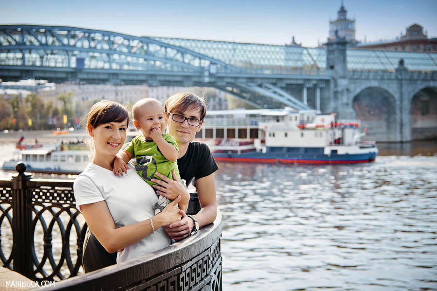 Parents and young son enjoyed the sunshine against the backdrop of the river and the ship.