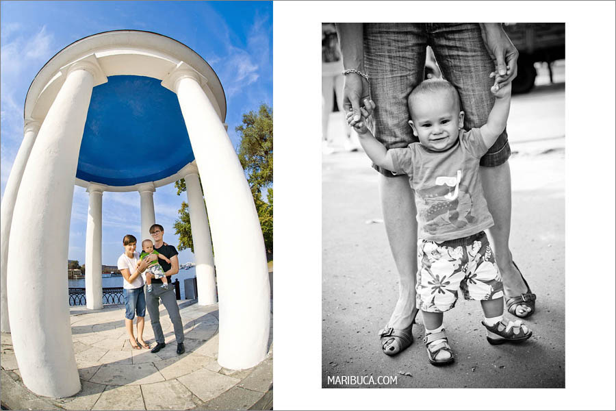 Family with 10 month old son standing on a background of white columns and sunny weather on a summer day.