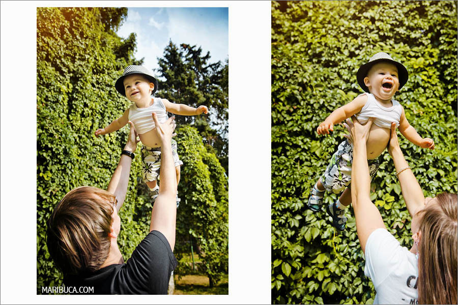A small child in a gray hat can fly against the background of a green bush and sky.