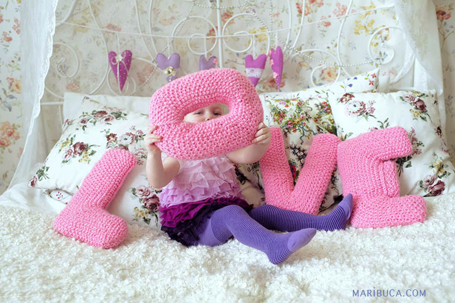 """One year old girl who is sitting on the bed in white and holding a pink """"O"""" letter connected with LOVE word."""