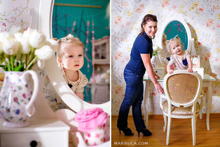 12 month old girl looks at herself in the mirror on and next to the mirror are white tulips in a vase. Mom and daughter stand on the background of white wallpaper with flowers.