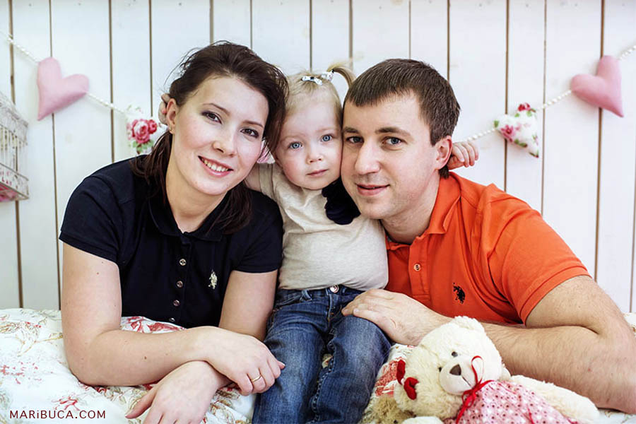 Little twelve month old girl in a white blouse and blue jeans hugs her parents on a white background.