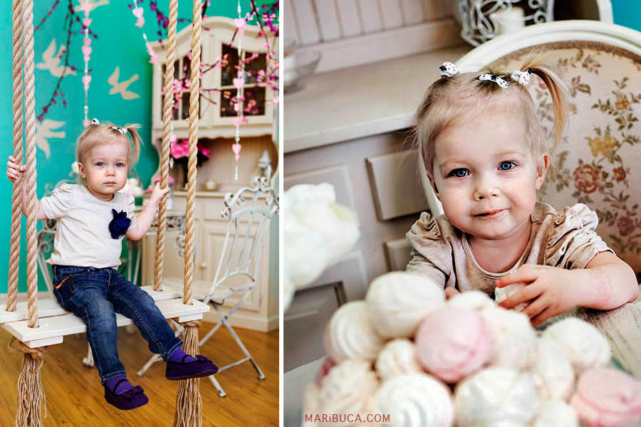 A little twelve month old girl in a white blouse and blue jeans is sitting on a rope swing. The little girl eats sweets.