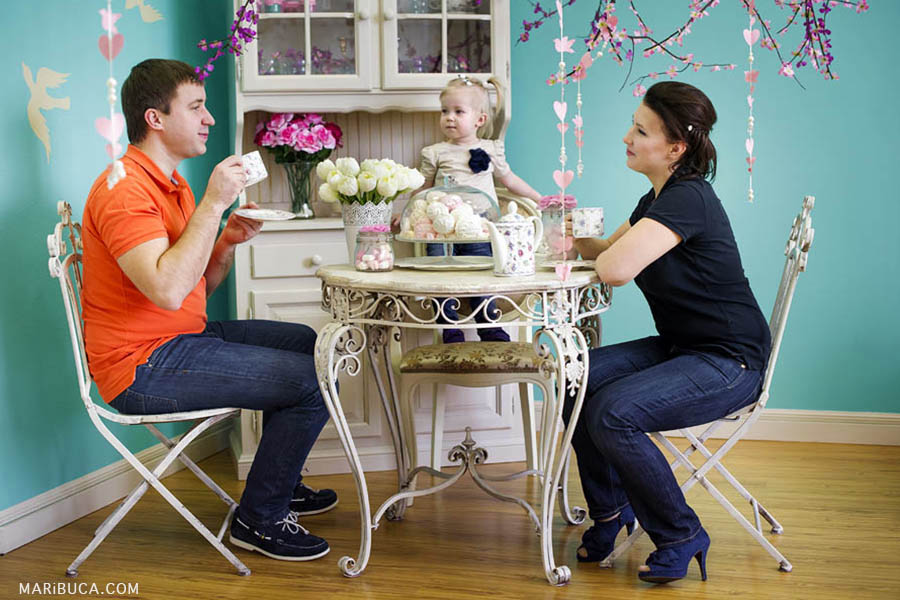 Parents sit on each other and look at each other and their little 12 month daughter looks like parents drink tea and talk.