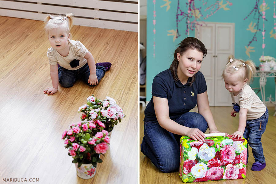 A little twelve month old girl in a white blouse and blue jeans is sitting on the floor with fresh pink flowers in pots. Mom and daughter are watching what's in the color case.
