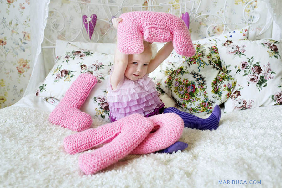 """Twelve month little girl in a light lilac and purple tights dress holds letter """"E"""" of the full word LOVE"""
