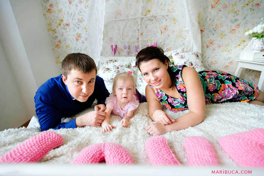 Parents with her little baby daughter lay down in the white bad in the room.