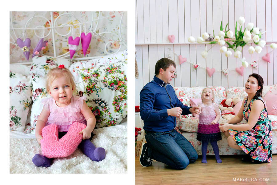 A little twelve-month-old girl in a light lilac dress sits on the bed. Parents with one year old daughter throw white tulips up and laugh.
