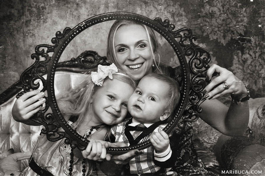 Retro photo where mom and her children laugh and look through the round frame.