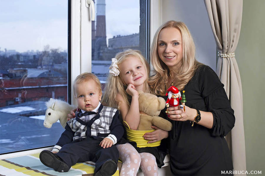 A mother with a five-year-old daughter and a one-year-old son are sitting on the windowsill against the window.