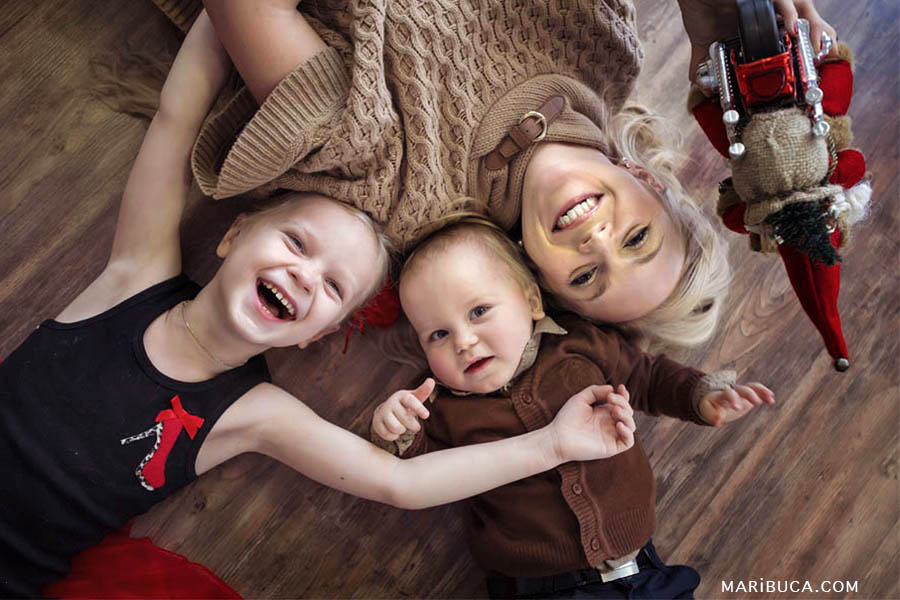 family of three people: my mother, the eldest daughter of five-year and year-old son lie on brown Laminated floor and laughing.