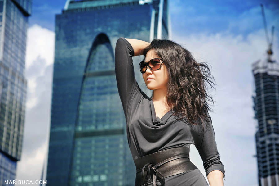 Lady in gray dress and sunglasses looks into the distance against the background of skyscrapers in San Francisco