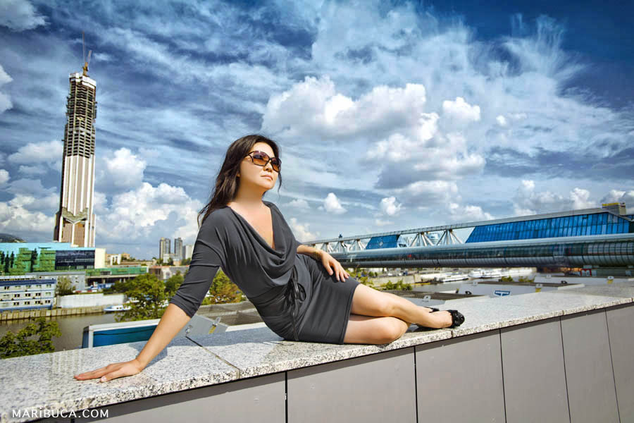 Girl in a gray dress and sunglasses sitting on the side of the building on a background of deep blue sky with white clouds.
