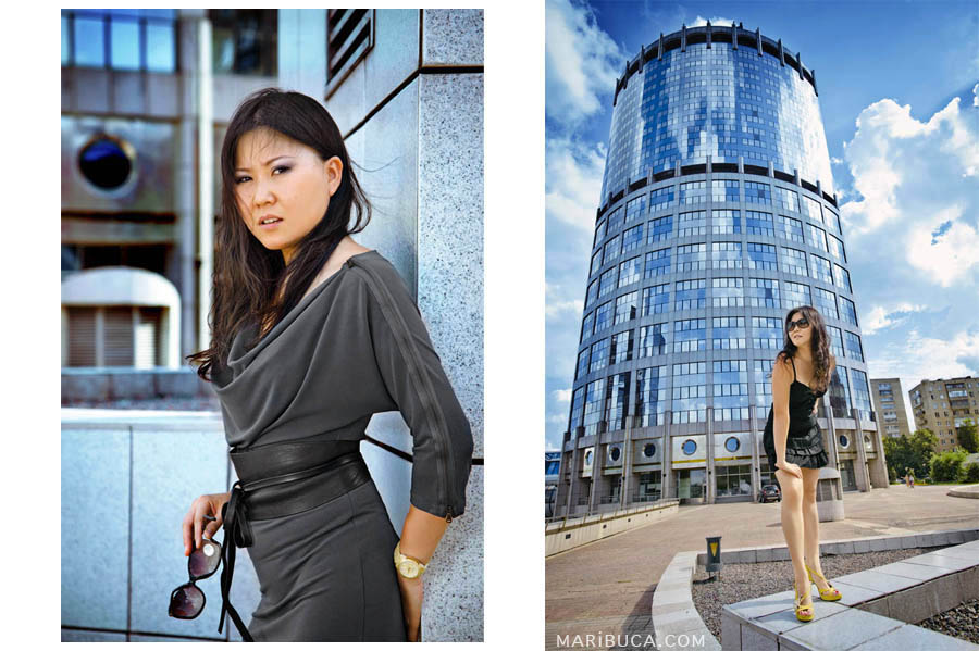 portrait of a girl in a gray dress leaned against a light gray wall. A girl in a black dress stands on the background of a high-rise in the downtown.