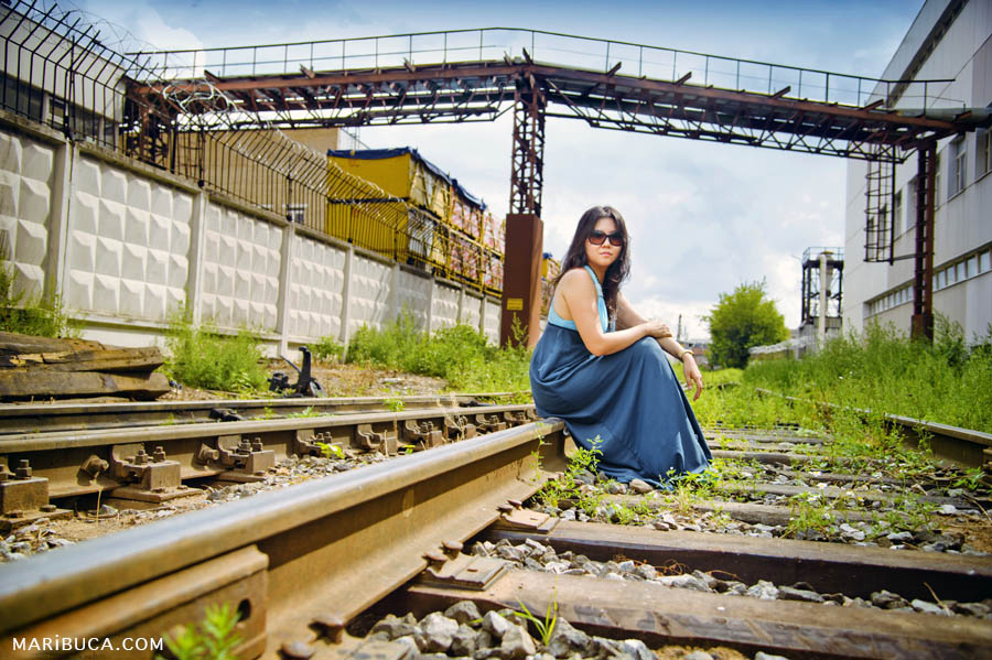 The girl in the blue-blue dress and sunglasses sits on the rails in industrial place